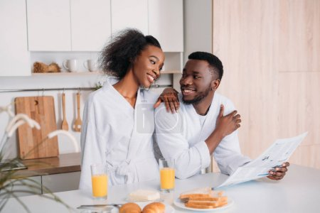 Young man with newspaper talking to smiling girlfriend in kitchen