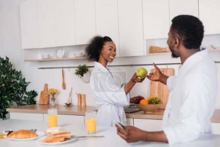Smiling woman giving apple to boyfriend in kitchen
