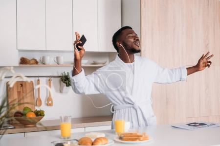 Photo for Young african american man in earphones listening to music from smartphone - Royalty Free Image