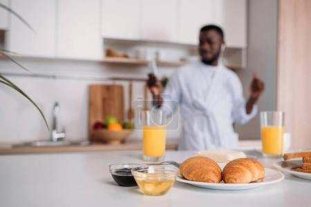 Close up view of croissants on plate, orange juice, jams and butter with young man in earphones on blurred background