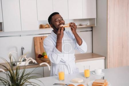 Photo for Young african american man eating toast in kitchen - Royalty Free Image