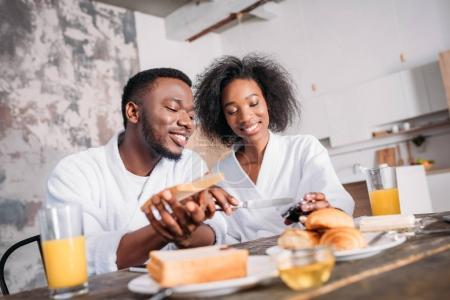 Smiling couple spreading jam on toast at table with breakfast