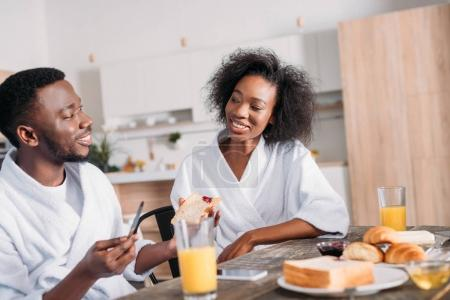 Smiling man spreading jam on toast and girlfriend sitting at table with breakfast