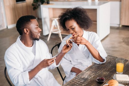 Young man feeding girlfriend at table in kitchen