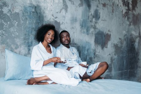 Young african american couple with coffee cups in bed