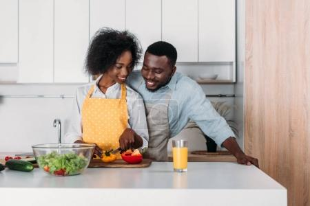 African american couple in aprons standing at table and cooking