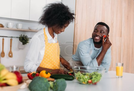 Photo for Smiling african american couple in aprons cooking in kitchen - Royalty Free Image