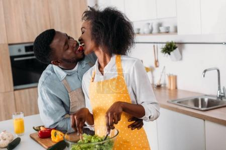 Young couple eating cherry tomato and mixing salad in bowl