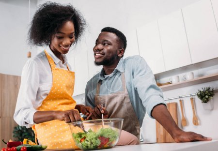 Photo for Low angle view of smiling woman mixing salad in bowl and sitting on table with boyfriend standing near - Royalty Free Image
