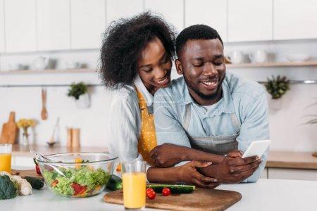 Photo pour Jeune homme tapant sur smartphone et copine debout derrière - image libre de droit