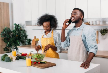 Photo for Woman mixing salad and boyfriend talking on smartphone in kitchen - Royalty Free Image