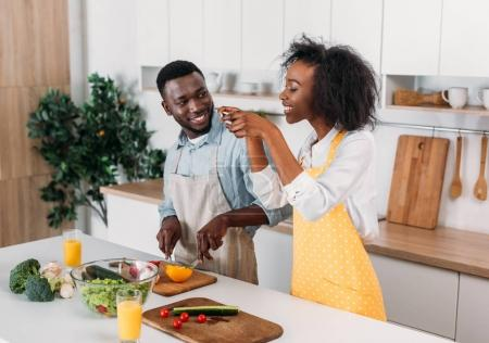 Photo for Smiling woman taking photo of food at table while boyfriend cutting pepper - Royalty Free Image