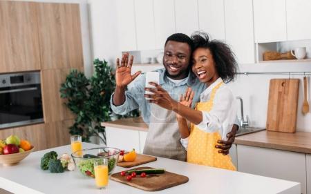 Photo pour Smiling couple afro-américain en tabliers prenant selfie dans cuisine - image libre de droit