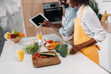 Couple looking at recipe on digital tablet while standing at table with vegetables