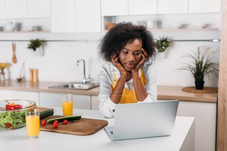 African american woman watching laptop at table in kitchen