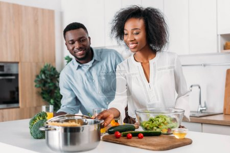 Young smiling couple standing at table with vegetables, salad and pasta in saucepan