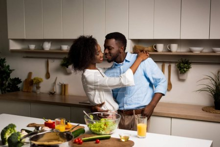 Photo for Young african american couple embracing in kitchen - Royalty Free Image