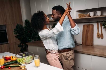 Photo pour Couple d'américains Arican danser près de table avec de la nourriture dans la cuisine - image libre de droit