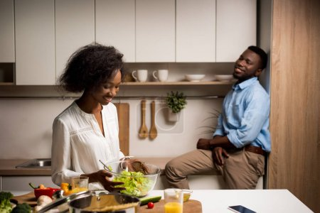 Photo for Woman holding bowl with salad while boyfriend sitting behind - Royalty Free Image
