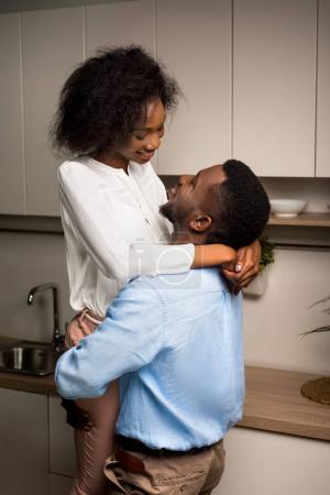 African american man raising smiling girlfriend in kitchen