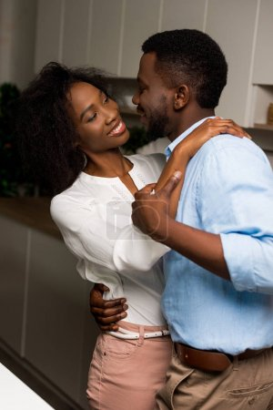 Young smiling african american couple dancing in kitchen