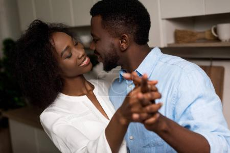 Smiling african american couple holding each other hands