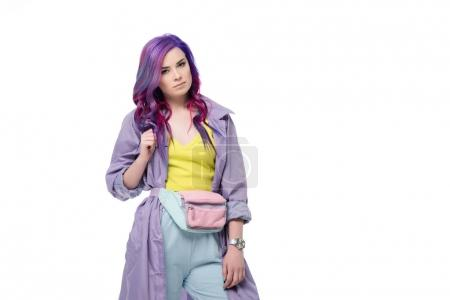 Attractive young woman with purple hair in trench coat with waist pack isolated on white