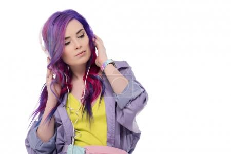 beautiful young woman with colorful hair in purple trench coat listening music with headphones isolated on white