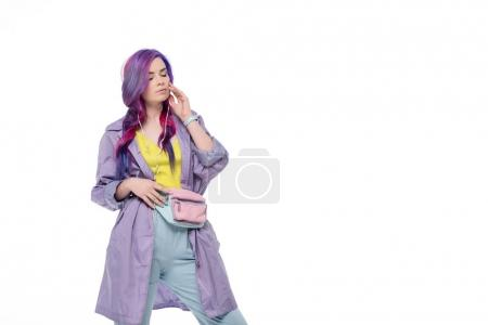 beautiful young woman in purple trench coat listening music with headphones isolated on white