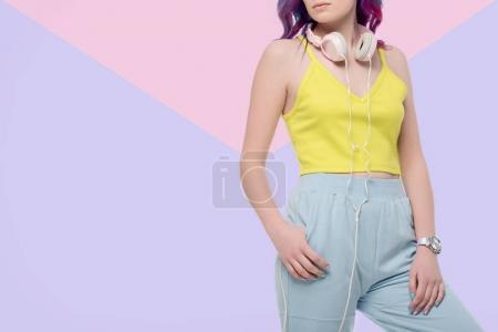 Photo pour Recadrée tir de femme avec un casque accroché sur cou sur fond créatif - image libre de droit