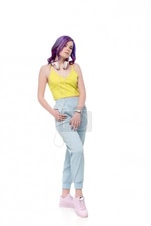 Attractive young woman with purple hair and headphones hanging on neck isolated on white