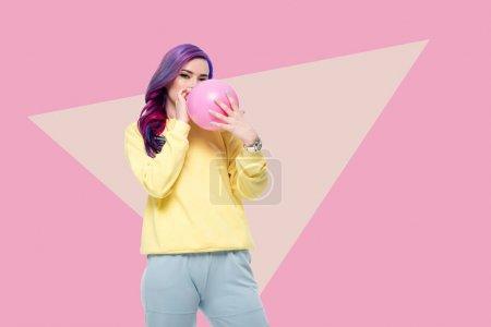 Beautiful young woman blowing up balloon on creati...