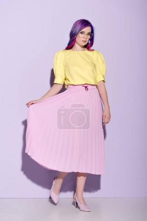 attractive young woman with colorful hair in skirt on pink