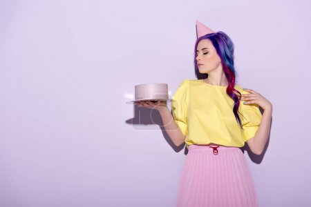 beautiful young woman in party hat with colorful hair holding birthday cake