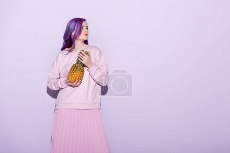 beautiful young woman with colorful hair and pink sweatshirt holding pineapple on pink