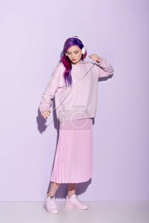 Dancing young woman with purple hair in pink clothes listening music with wired headphones