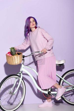 Photo pour Jolie femme en rose vêtements sur vélo avec ananas et bananes dans le panier - image libre de droit
