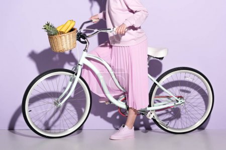 Photo for Cropped shot of woman in pink clothing on bicycle with pineapple and bananas in basket - Royalty Free Image