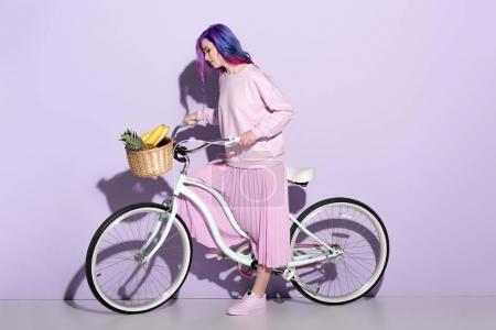 Foto de Atractiva mujer joven en ropa rosa en bicicleta con piña y los plátanos en la cesta - Imagen libre de derechos