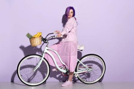 side view of young woman in pink clothing on bicycle with pineapple and bananas in basket