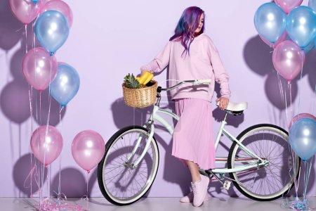 Photo pour Belle jeune femme en rose vêtements sur vélo avec ananas et bananes dans le panier - image libre de droit