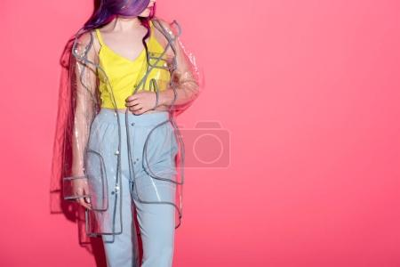 cropped shot of fashionable woman in transparent raincoat on red