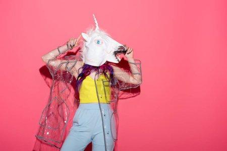 Photo pour Femme dansante en imperméable transparent à la mode et masque de licorne sur rouge - image libre de droit