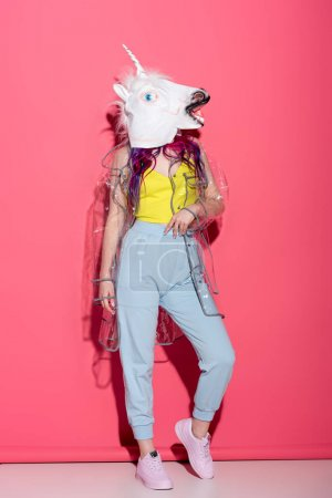Photo for Stylish woman in fashionable transparent raincoat and unicorn mask on red - Royalty Free Image