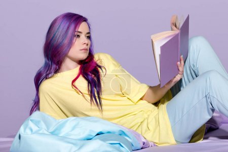 serious young woman with colorful hair reading book in bed