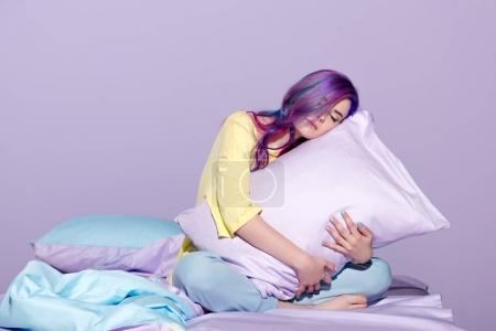 sleepy young woman sitting in bed and embracing pillow