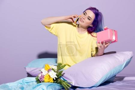 Photo for Happy young woman with gift box and flowers sitting in bed and talking by phone - Royalty Free Image