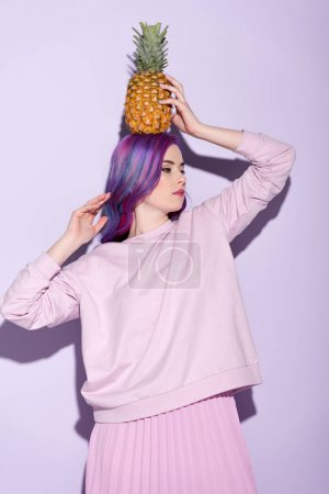 beautiful young woman in pink sweatshirt holding pineapple on head