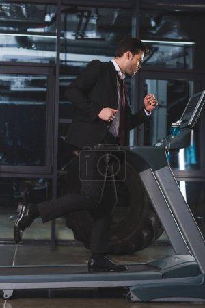 Photo pour Bel homme d'affaires courir sur tapis roulant dans la salle de gym - image libre de droit