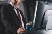 cropped view of businessman training on treadmill and taking sport bottle in gym